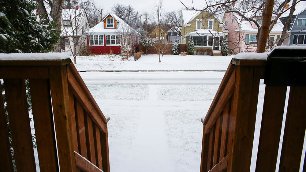 A view from a home's front porch, looking down the steps and onto a snow-covered residential street.