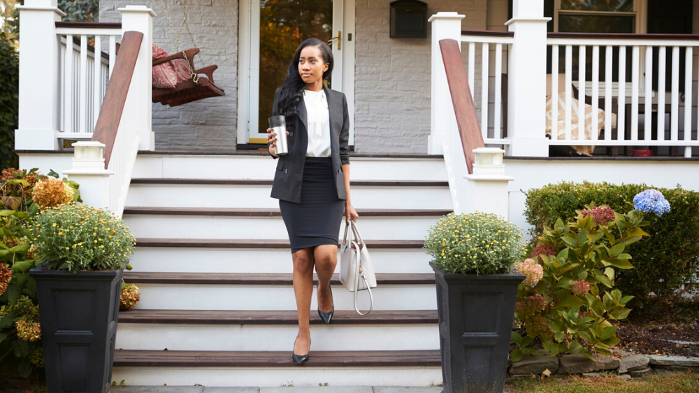 Business woman leaving home holding a thermos